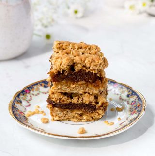 Two squares of date square stacked on a plate. Coffee mug a creamer cup in the background with white flowers.