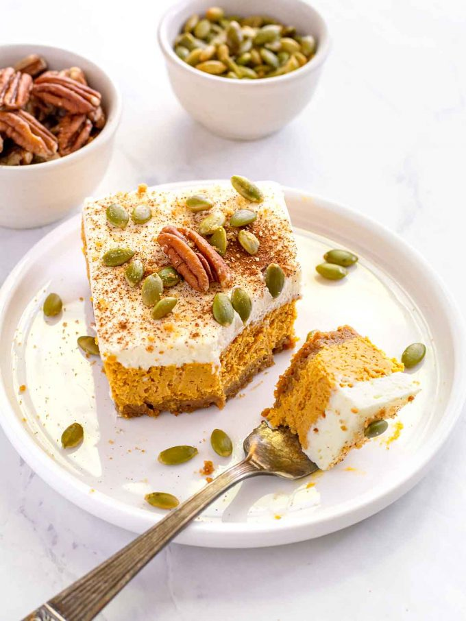 Square of pumpkin cheesecake, topped with whipped cream, a whole pecan and pumpkin seeds sitting on a white plate. Bowl of pecans and pumpkin seeds in background.