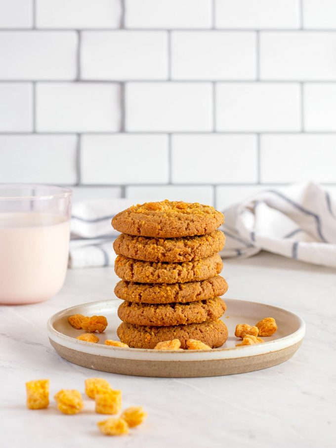 six golden cookies stacked into a tower on a plate