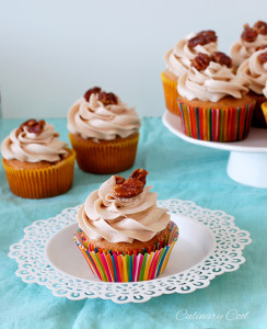 cupcake on a small white plate, with several other cupcakes in background on cake stand