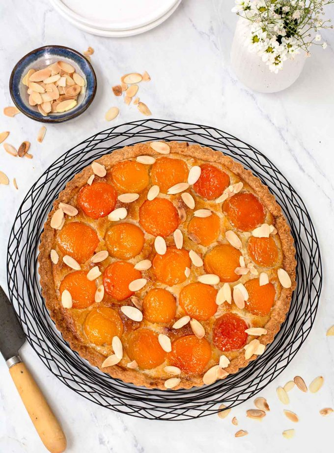 Round tart with apricot halves and sprinkled with sliced almonds. Tart is sitting on a round black wire rack. Small bowl of toasted almonds to the top left.