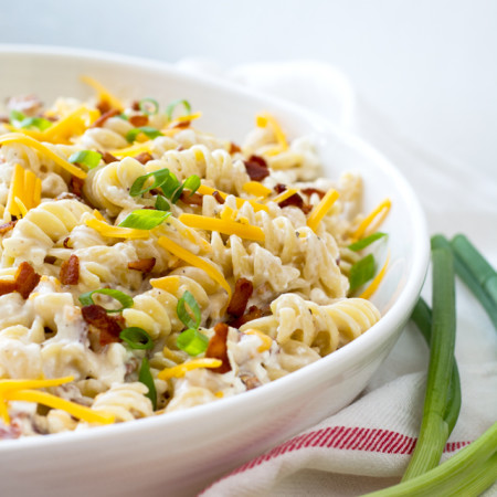Large white bowl sitting on a red-striped napkin, filled with rotini pasta, bacon, and green onions