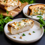 A small plate with a slice of garlic toast topped with cream cheese and parsley
