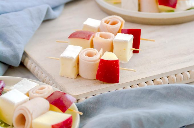 cubes of brie cheese, gala apples and deli turkey on cocktail skewers served on top of a green kale salad