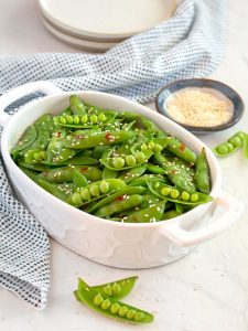 Small white serving dish filled with snap peas, sesame seeds in a small bowl in the background