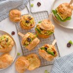Pâte à choux puffs, cut in half and filled with curried turkey salad, with decorative toothpicks through them to hold in place