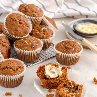 bran muffin cut in half with butter spread on one side. Several other muffins stacked on a cooling rack in the background
