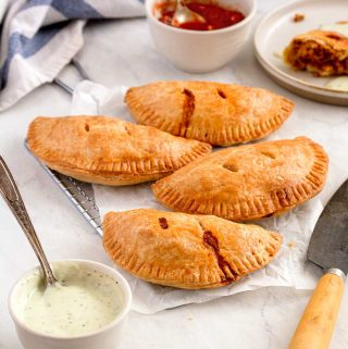 Four empanadas on a rectangle cooling rack, with two small dishes full of salsa and avocado sour cream