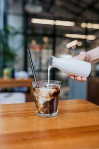 Glass filled with coffee with cream being poured over top
