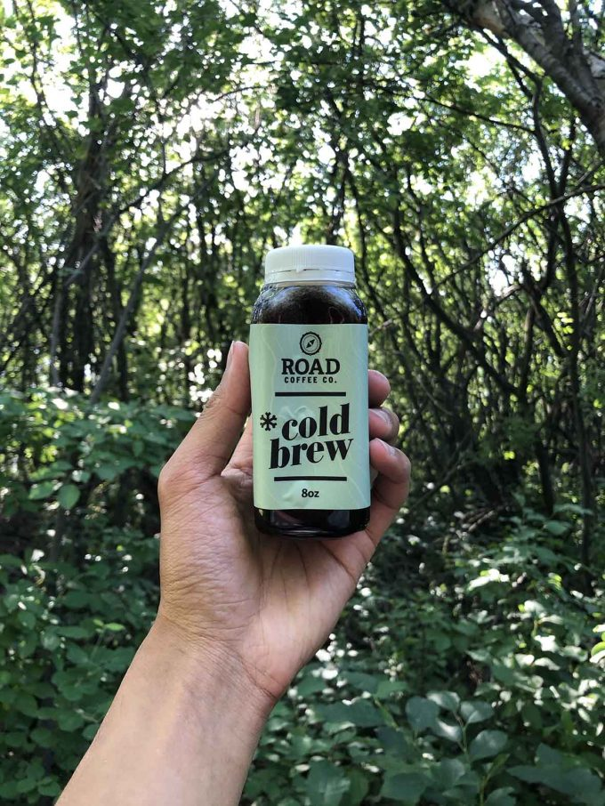 Small container of cold brew coffee held up in the air in a forest