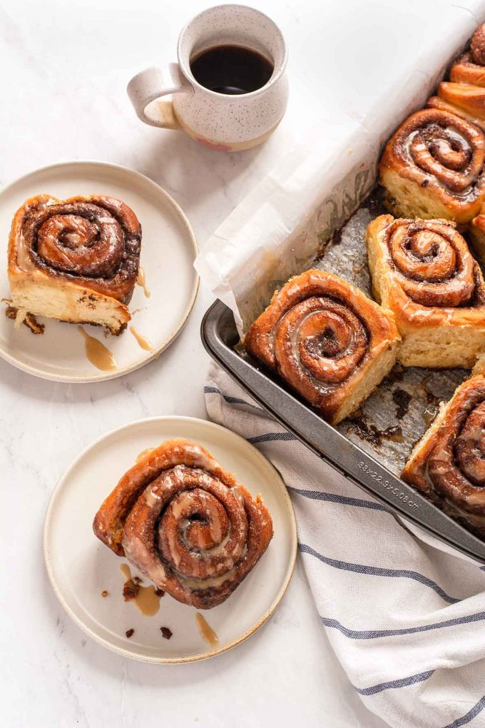 Glazed cinnamon rolls on plates with coffee in background
