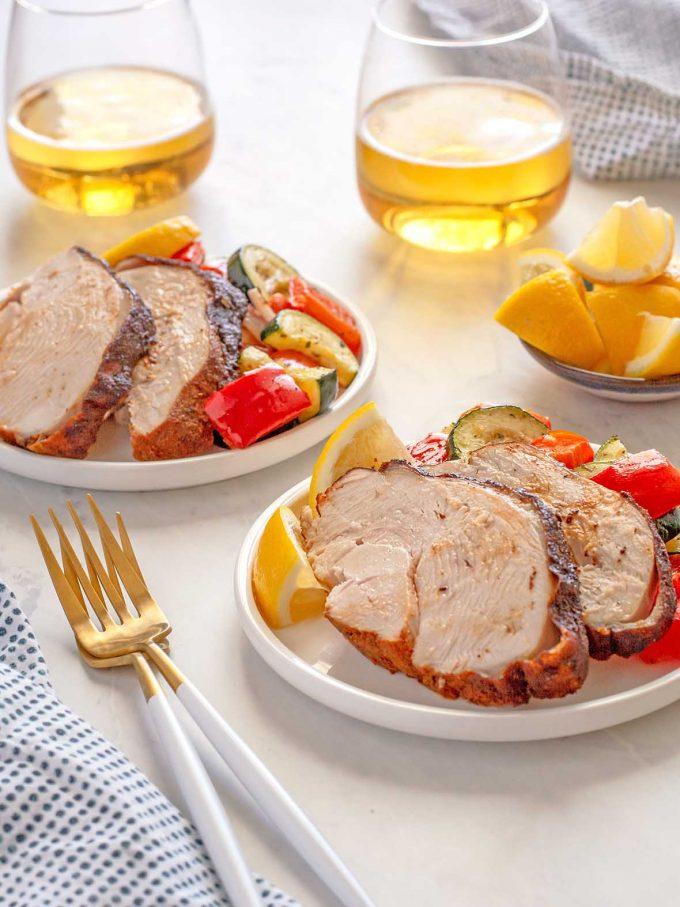 Sliced turkey breast sitting on roasted veggies on small plates.