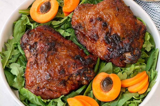 Two turkey thighs on a bed of greens, with apricot halves