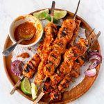 Cubes of cooked turkey on skewers, piled on a round wooden platter, with a small bowl of bbq sauce, limes and grilled red onions.