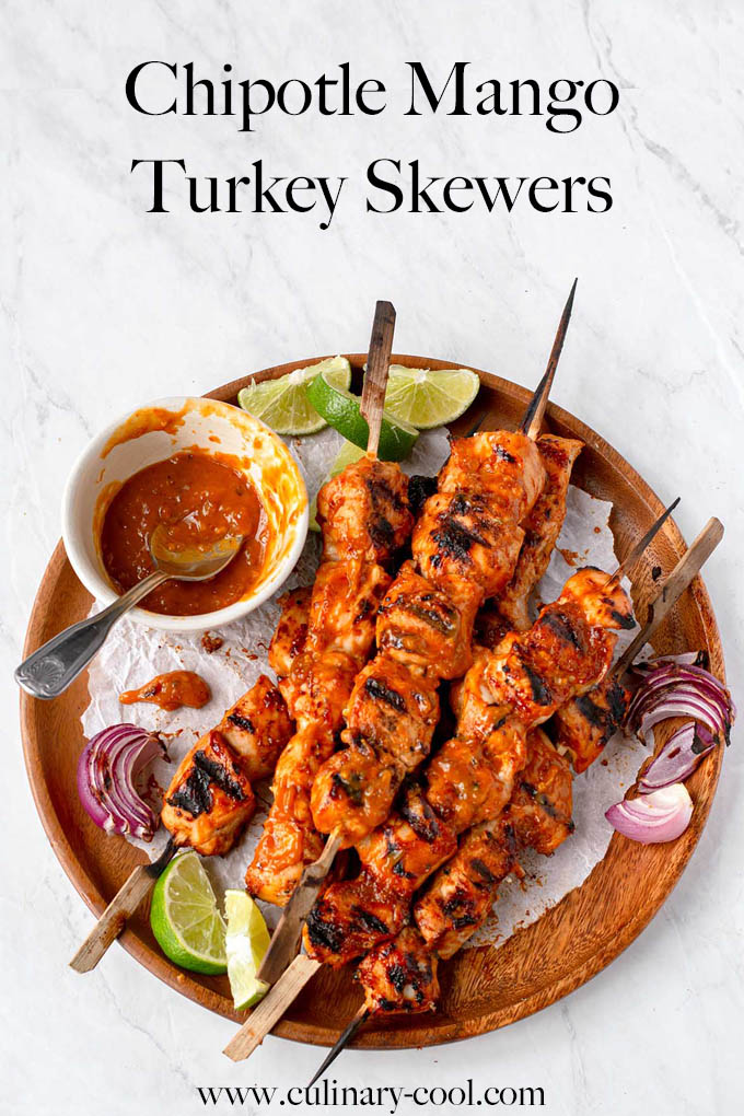 """Cubes of cooked turkey on skewers, piled on a round wooden platter, with a small bowl of bbq sauce, limes and grilled red onions. Text at top of page that says """"Chipotle Mango Turkey Skewers"""". Image for Pinterest"""